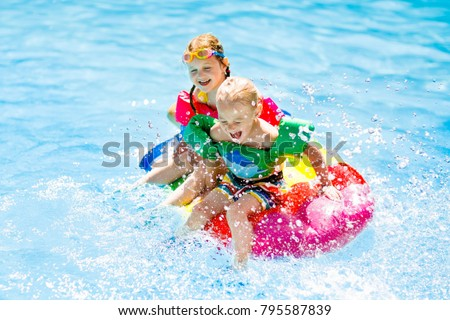 Boy and girl on inflatable ice cream float in outdoor swimming pool of tropical resort. Summer vacation with kids. Swim aids and wear for children. Water toys. Little child floating on colorful raft. #795587839