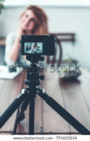 Toned bokeh image of woman blogger sitting on table with succulent in glass jar