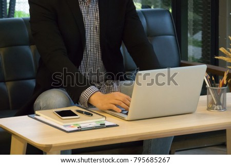 Business man wearing eye glasses and working with laptop on wooden table at modern office room.  #795685267