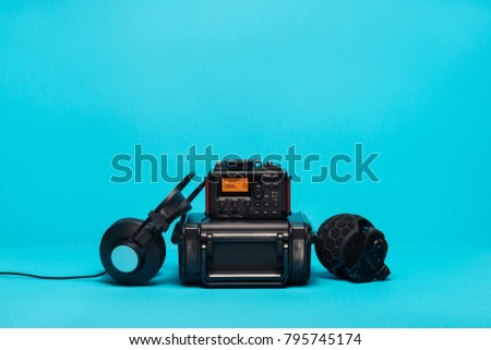 equipment for field audio recording on blue background. microphone, recorder, headphones and case.
