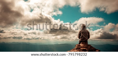 alone man sitting on the peak of mountain cloudy sky lonely scene, waiting for hope, landscape panorama view, copy space Royalty-Free Stock Photo #795798232