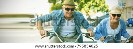 Happy mature couple going for a bike ride in the city on a sunny day #795834025