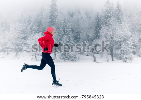 Woman running on snow in winter mountains. Sport, fitness inspiration and motivation. Young happy woman trail running in mountains on snow, winter day. Female trail runner jogging outdoors. #795845323