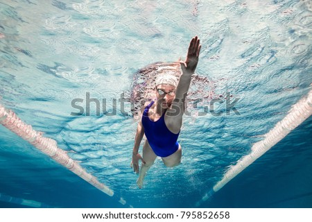 underwater picture of female swimmer in swimming suit and goggles training in swimming pool #795852658