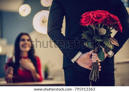 Beautiful loving couple is spending time together in modern restaurant. Attractive young woman in dress and handsome man in suit are having romantic dinner. Celebrating Saint Valentine's Day. #795913363