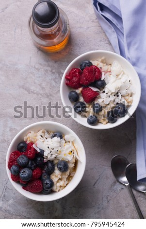 Overhead shot of oatmeal in white bowls served with coconut and blueberries . Rustic wooden background. A blue napkin. maple syrup and spoons next to the bowls.   #795945424