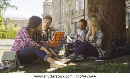 College students having discussion under tree on campus, preparing for exams #795947644