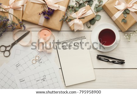 Wedding to do list top view. Present boxes, calendar for marriage planning and various bridal stuff on white rustic table. Memmorable date organization background #795958900