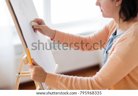 art, creativity and people concept - artist with eraser and still life picture of flower in vase on easel at studio #795968335