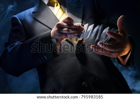 The man in a suit shuffles cards, in his sleeve he has a diamond ace #795983185