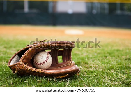 Old baseball and glove on field with base and outfield in background. Royalty-Free Stock Photo #79600963