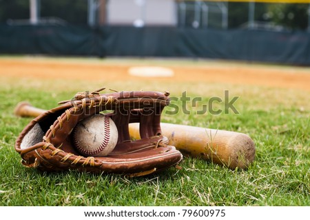 Old baseball, glove, and bat on field with base and outfield in background. Royalty-Free Stock Photo #79600975