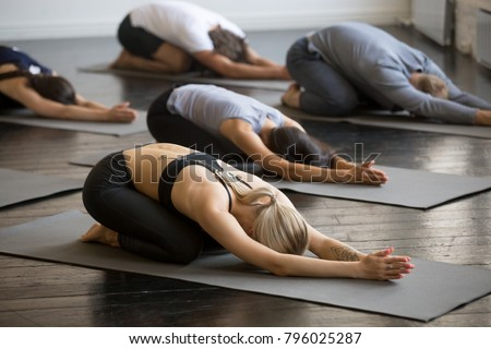 Group of young sporty people practicing yoga lesson with instructor, stretching in Child exercise, Balasana pose, working out, indoor close up, students training in club, studio #796025287