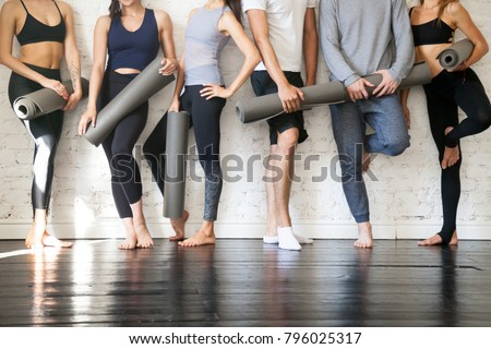 Group of young sporty people standing at wall. Students taking a rest from fitness activity, time to recover strength, waiting for a lesson to start in loft studio, close up. Healthy lifestyle concept #796025317