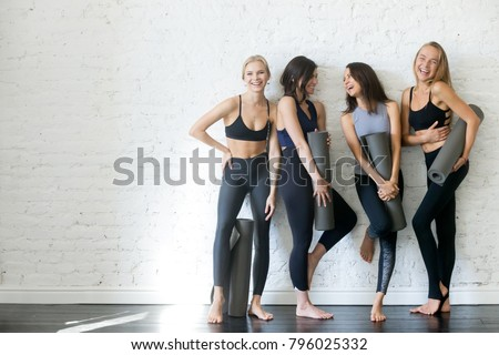 Group of young sporty girls with yoga mats standing at white wall. Female companions in gym resting after fitness, indoor full length, loft studio, copy space #796025332