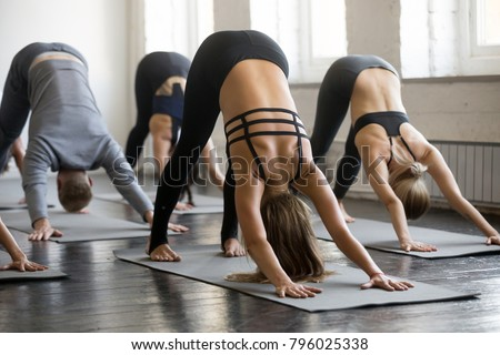 Group of young sporty people practicing yoga lesson with instructor, stretching in Downward facing dog exercise, adho mukha svanasana pose, working out, indoor full length, students training, studio #796025338