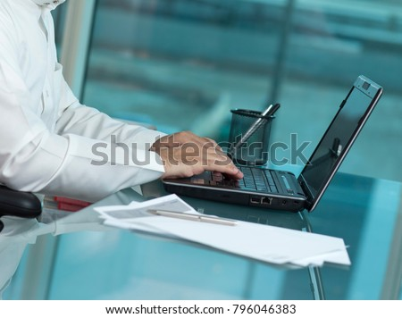Saudi Man Hands Typing On Laptop at His Desk. Headless
