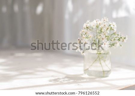 Small white daisies in a glass jar on a white table. #796126552