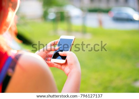 Close-up view of woman in red dress using her smart phone #796127137