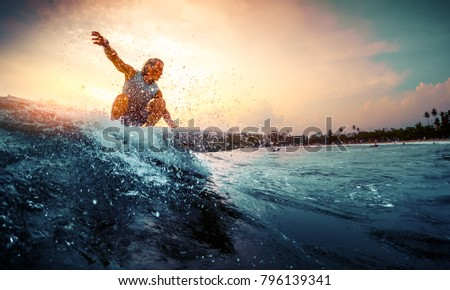 Young surfer rides the wave during sunset #796139341