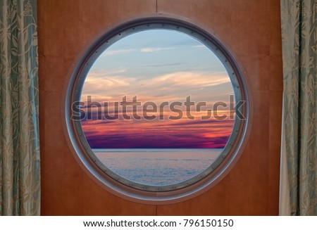 Ocean and evening sky sunset seen through the porthole of a ship #796150150