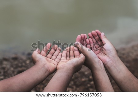 The hands of children who need water on an arid soil. #796157053