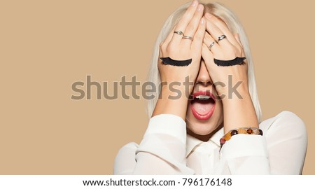 Funny young woman with eyelashes painted on the hand. Blonde hair girl closed her eyes with hands and waiting for surprise. Surprised model in white shirt. Concept of fun and merriment. #796176148