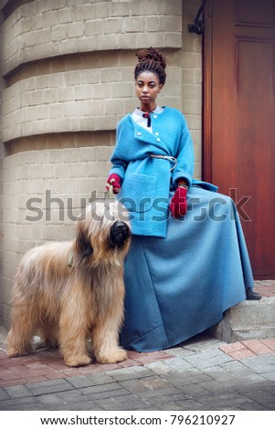 Fashionable African woman in a blue vintage dress is standing with dog breed Briard on the street on a background of gray wall outdoor #796210927
