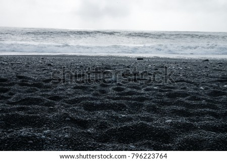 The Black sand beach of Reynisfjara, Vik and the mount Reynisfjall from the Dyrholaey promontory and Volcanic rock in the southern coast of Iceland with eroded stone arch visible in distance #796223764