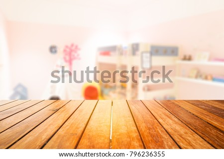 Wooden board empty table in front of blurred background.Perspective light wood over blur in kid or baby room interior- can be used for display or montage your products. Mock up for display of product.