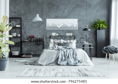 Grey bedsheets on bed and ficus in bright bedroom interior with poster on concrete wall and lamps #796275481