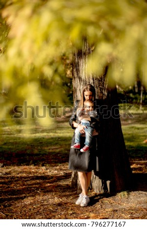 Young mother and baby boy in autumn park at sunny day #796277167
