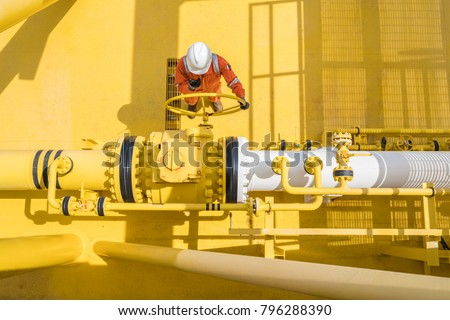 Production operator communicate between central control room by using radio to operate ball valve at offshore oil and gas processing platform for control gases and liquid crude oil process.  Royalty-Free Stock Photo #796288390