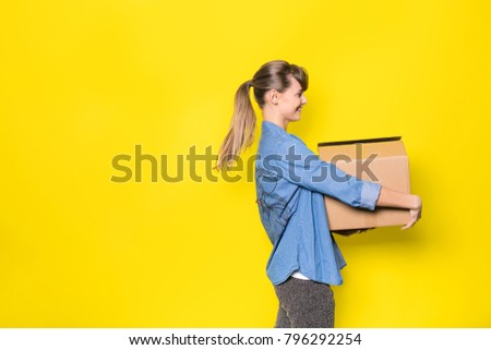 pretty woman standing on yellow background with moving cardboard box #796292254