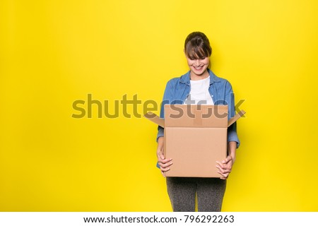 pretty woman standing on yellow background with moving cardboard box #796292263