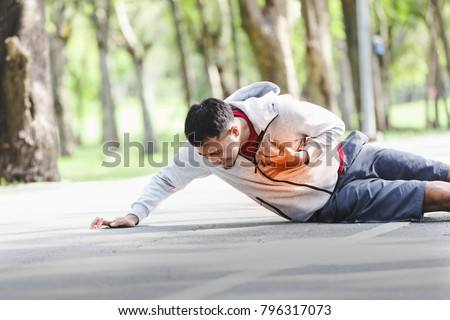 Asian cardiac arrest running young man heart attack in park.Severe heartache,First aid to people with heart disease. Royalty-Free Stock Photo #796317073