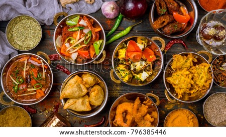 Assorted indian food set on wooden background. Dishes and appetisers of indeed cuisine, rice, lentils, paneer, samosa, spices, masala. Bowls and plates with indian food top view #796385446
