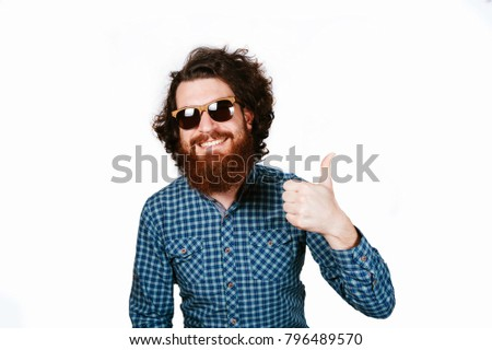 Life style and people concept: Happy handsome man with beard in sunglasses showing thumbs up. Smiling happy hipster man with beard over white background. Man with curly hair and beard. Smile. #796489570