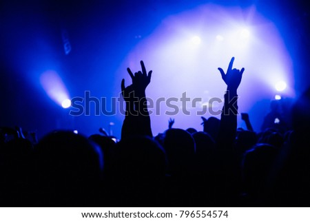 Raised hands with sign of horns. Concert stage on the background. Violet lighting. #796554574
