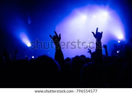 Raised hands with sign of horns. Concert stage on the background. Violet lighting. #796554577