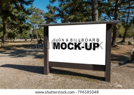 The mock up blank white screen big wooden billboard at park or tourist attraction with clipping path, for advertisement  or information and map of that area, and beautiful garden background