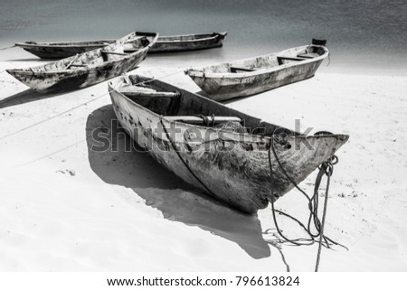 Beautiful Zanzibar coast line. Wooden fisherman boats on sandy beach. Black and white picture, Zanzibar, Tanzania
