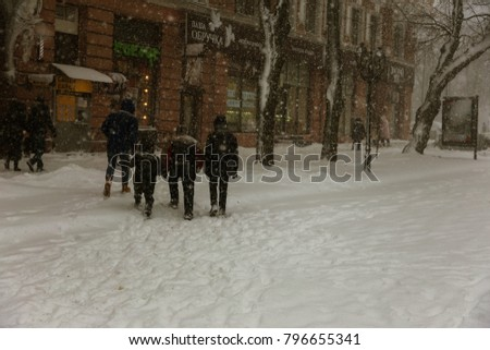 ODESSA, UKRAINE-January 16, 2018: Strong snowfall, cyclone in city streets in winter. Cars are covered with snow. Slippery road. Bad weather in winter: heavy snow and snowstorm. Pedestrians go on snow #796655341