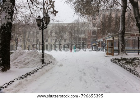 ODESSA, UKRAINE-January 16, 2018: Strong snowfall, cyclone in city streets in winter. Cars are covered with snow. Slippery road. Bad weather in winter: heavy snow and snowstorm. Pedestrians go on snow #796655395