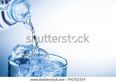 pouring water from plastic bottle into glass against blue gradient #796702354