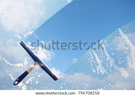 Rubber squeegee cleans a soaped window and clears a stripe of blue sky with clouds, concept for tranparency or spring cleaning, copy space in the background Royalty-Free Stock Photo #796708258