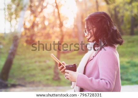 Woman with smartphone and hot drink outdoor #796728331