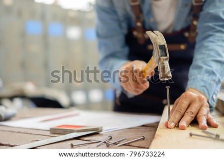 Carpenter working on woodworking machines in carpentry shop. A man works in a carpentry shop. Royalty-Free Stock Photo #796733224