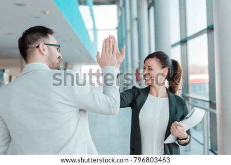 Two business people high-five. Job well done. #796803463