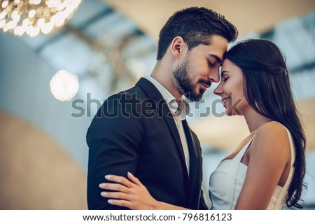 Beautiful loving couple is spending time together in modern restaurant. Attractive young woman in dress and handsome man in suit are having romantic dinner. Celebrating Saint Valentine's Day. #796816123